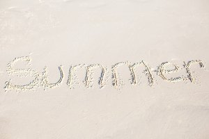 Word Summer handwritten on sandy beach with soft ocean wave on background