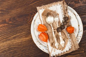 Tableware and silverware with autumn decorations on the wooden background