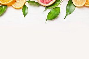 Citrus fruits slices border on white