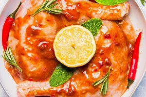 Raw chicken legs with spicy sauce