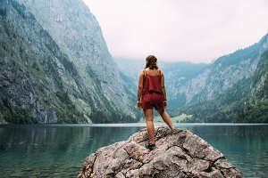 Young woman standing on rock looking at beautiful and misty lake