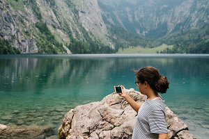 Young woman taking photos at beautiful and misty lake