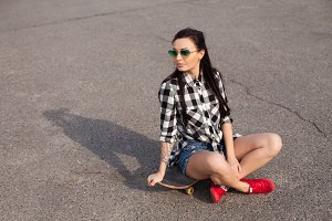 The woman sits on skate