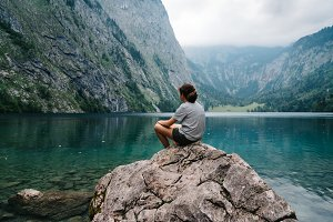 Girl sitting on rock looking at beautiful and misty lake in the