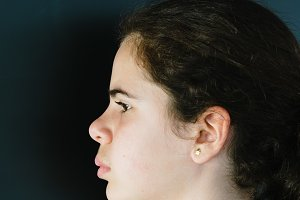 Headshot portrait of serious teenager. Side view