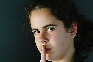 Defiant teenager with finger on lips.