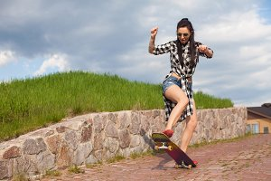The woman does a trick with skate