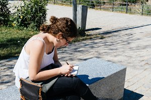 Young woman artist drawing sketches in a park