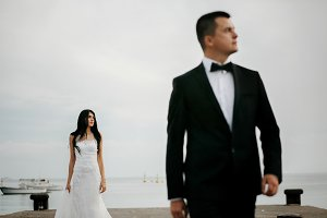 Thoughtful bride stands behind groom