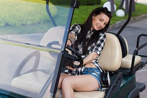 The woman is in a golf cart