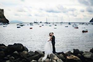 Wedding couple stands on the rocks