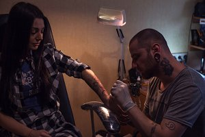 Tattooer makes tattoo for woman