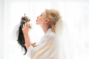 Bride plays with funny fluffy dog