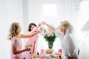 Bride in white robe and bridesmaids