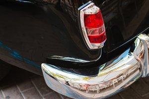 Close-up of back headlight of black vintage car.