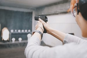 Woman shooting with a gun in shooting gallery