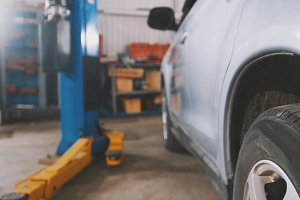 Car service - white vehicle in workshop for repairing or checking
