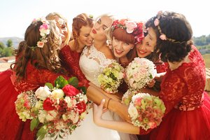 Bride enjoys hugs of her bridesmaids