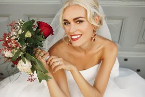 Blonde bride holds her bouquet
