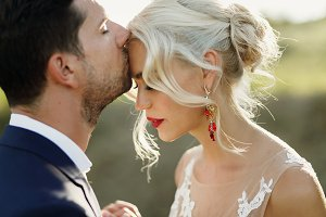 Bride bends her head to groom