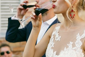 Bride with red lips drinks red wine