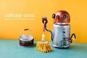 Web site under construction. Robot washer with mop and bucket of water