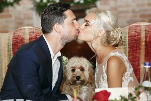 Bride and groom kiss over curly dog