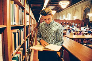 Student man reading book in library