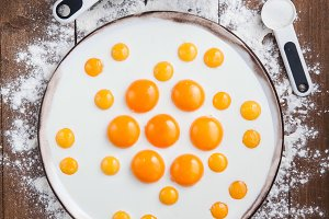 Egg yolks patern on a white plate, flat lay, top view