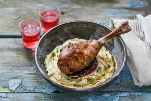 Baked turkey leg with cranberry sauce on mashed celery root, rustic style