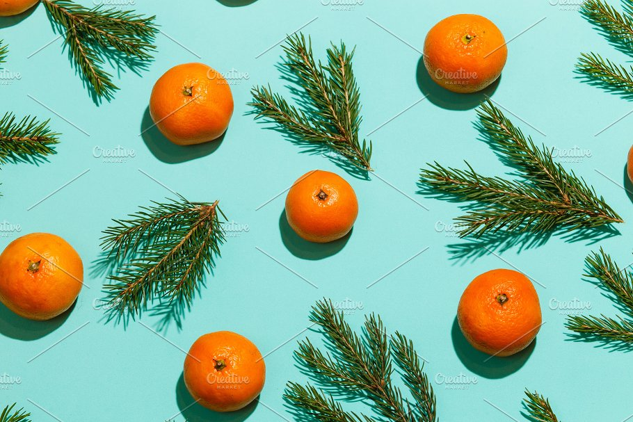 pattern of tangerines and fir branches on aquamarine table new year background top view