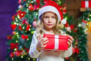 Little girl sitting by the tree holding a Christmas gift In the