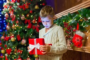 boy with Christmas gift Opening Christmas Present In Front Of Tr