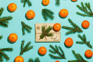 Christmas composition with tangerines, fir branches and handmade gift. Flat lay, top view