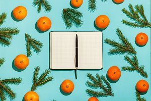 Christmas composition. Christmas frame with tangerines, fir and opened diary on green table. Flat lay, top view