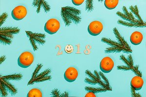 New year composition 2018. Christmas frame with tangerines, fir branches, and wooden lettering 2018 with smile. Flat lay, top view