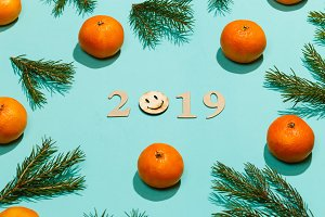 New year composition 2019. Christmas frame with tangerines, fir branches, and wooden lettering 2019 with smile. Flat lay, top view