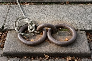 Old iron rings with rope and knot mooring a boat