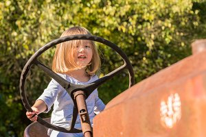 Young girl driving an old tractor on farm