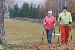 Two happy elderly woman in autumn park have nordic walking among autumn cold park