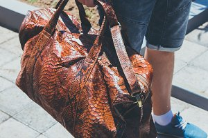 Young handsome man with luxury snakeskin python travel bag. Bali island, Indonesia.
