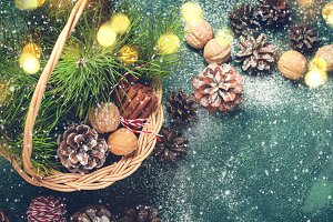 Christmas background. Basket with fir cones and branches, nuts and cinnamon