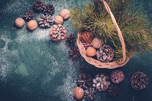 Christmas background. Basket with fir cones and branches, nuts a