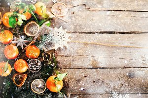 Magic Christmas background - vintage wood, candy cane, house, cinnamon, star anise, sweet mandarins with green leaves, cones, snowflakes. New Year. Top view, copy space, snow, bokeh.