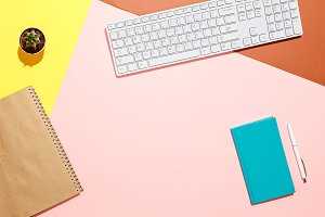 Modern positive workspace. Flat lay composition of keyboard, cactus, diary with pen on colorful desk. Pink, yellow, aquamarine and and brown colours