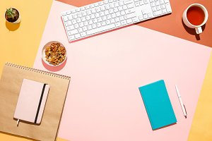 Modern feminine home workspace. Flat lay composition of keyboard, cactus, diary with pen and cup of tea on colorful desk. Pink, yellow, aquamarine and and brown colours. Blogger's home office.