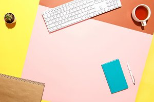 Trendy home office workspace. Flat lay composition of keyboard, cactus, diary with pen and cup of tea on colorful desk. Pink, yellow, aquamarine and and brown colours. Blogger's home office