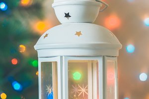 Christmas white lantern with a burning candle on the background of a Christmas tree, lights of garlands, bokeh.