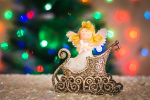 Christmas toy angel in a sleigh against the background of a Christmas tree, lights of garlands, bokeh.