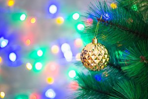 Christmas golden ball on a Christmas tree on a background of sparkles of garlands, bokeh.